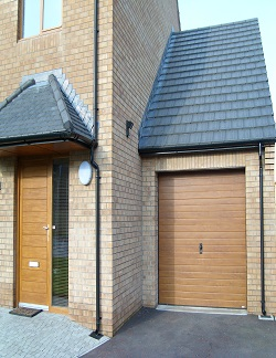 ThermAdor insulated sectional door Narrow Ribbed Woodgrain Smooth Golden Oak with manual lock